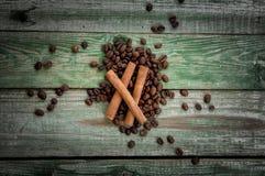 Koffiebonen en kaneel op groene houten lijst Stock Foto