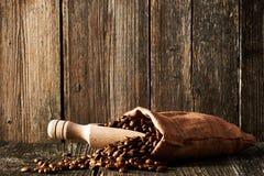 Koffiebonen en lepel in zak Stock Afbeelding