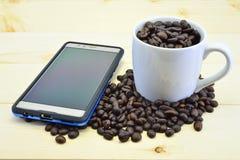 Koffiebonen en mobiel Stock Afbeeldingen