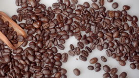 Koffiebonen en olijf houten lepel op witte achtergrond stock video