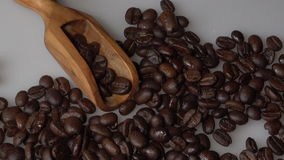 Koffiebonen en olijf houten lepel op witte achtergrond stock footage
