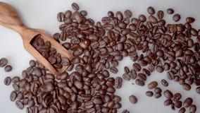 Koffiebonen en olijf houten lepel op witte achtergrond stock videobeelden