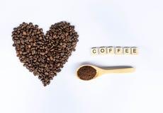 Koffiebonen in hart met koffiewoord dat wordt gevormd stock foto