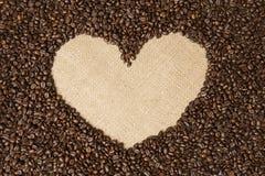 Koffiebonen in hartvorm op achtergrondstoffen van jute Stock Afbeelding