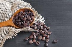 Koffiebonen in houten lepel en dichtbijgelegen stock foto