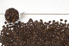 Koffiebonen in kop op witte hout en boon Stock Afbeelding
