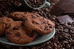 Koffiebonen met chocolade en koekjes in een kop en een plaat royalty-vrije stock afbeelding
