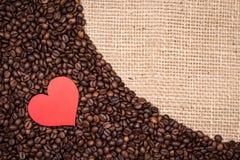 Koffiebonen met rode hart en jutetextiel Royalty-vrije Stock Foto's