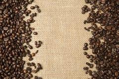 Koffiebonen op de achtergrond van jutestoffen Royalty-vrije Stock Afbeelding