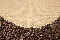 Koffiebonen op de achtergrond van jutestoffen Stock Foto's