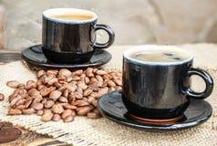 Koffiebonen op een houten raad en een kop van koffie Stock Foto's