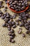 Koffiebonen op houten lepel en Jute Stock Foto