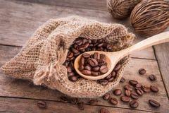 Koffiebonen op houten lepel in zak Stock Foto's
