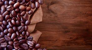Koffiebonen op houten lijst uitstekende stijl als achtergrond voor grafisch ontwerp stock foto's