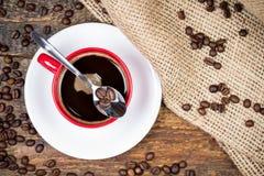 Koffiebonen op lepel bovenop koffiekop Stock Afbeelding