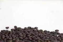 Koffiebonen op wit gebied als achtergrond voor exemplaarruimte Stock Foto's