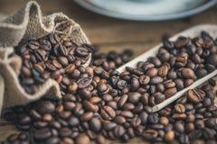 Koffiebonen uit Jutezak die worden gemorst stock foto's