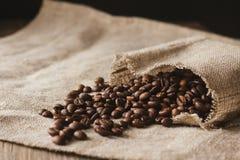 Koffiebonen van linnenzak die worden uitgespreid Stock Afbeelding