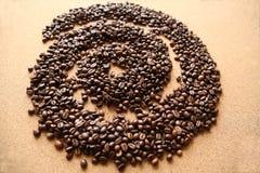 Koffiebonen in vorm van spiraal op houten achtergrond stock foto