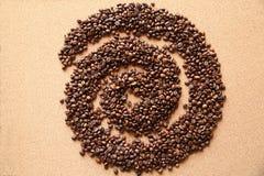Koffiebonen in vorm van spiraal op houten achtergrond stock afbeeldingen