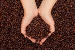 Koffiebonen in women& x27; s handen op de achtergrond van koffiebonen Stock Afbeeldingen