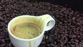 Koffiedaling die in langzame motie binnen van kop van espresso Italiaanse koffie vallen met schuim op de achtergrond, het voedsel stock footage
