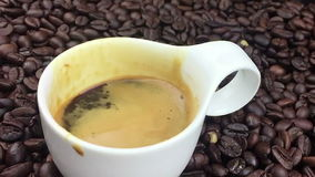 Koffiedaling die in langzame motie binnen van kop van espresso Italiaanse koffie vallen met schuim op de achtergrond van koffiebo stock videobeelden