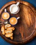Koffieespresso, koekjes en melk bij het houten dienen om raad stock foto