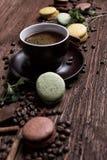 Koffiekop, bonen, chocolade en kleurenmakarons op de lijst Royalty-vrije Stock Foto