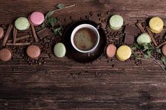 Koffiekop, bonen, chocolade en kleurenmakarons op oude keukenlijst Stock Afbeeldingen