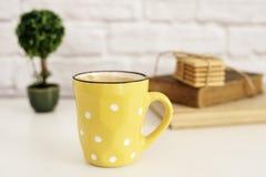 Koffiekop, cappuccino, latte, oude boeken, koekjes en bonsai op witte lijst Gray Brick Wall Het concept van de vrije tijdslevenss stock foto's
