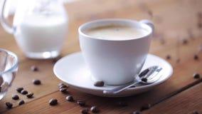 Koffiekop en bonen die aan houten lijst gieten stock footage