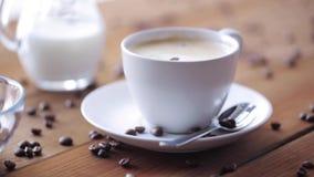 Koffiekop en bonen die aan houten lijst gieten stock video
