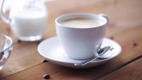 Koffiekop en bonen die aan houten lijst gieten stock videobeelden