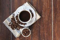 Koffiekop en bonen op het hout Stock Afbeelding