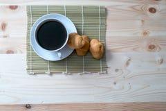 Koffiekop en croissant op houten achtergrond Stock Foto's