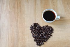 Koffiekop en hart-vormige koffiebonen stock afbeelding