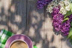 Koffiekop en kleurrijke lilac bloemen op tuinlijst royalty-vrije stock afbeelding