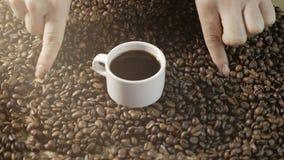 Koffiekop en koffiebonen De vrouwen` s handen trekken een hart van koffiebonen Een witte Kop van het stomen van koffie met geroos stock video