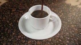 Koffiekop en koffiebonen Een witte kop van verdampende koffie op de lijst met geroosterde boon De langzame Motiekoffie giet stock footage