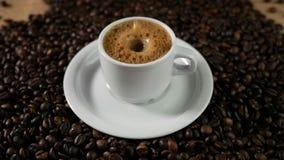 Koffiekop en koffiebonen Een witte kop van verdampende koffie op de lijst met geroosterde boon De langzame Motiekoffie giet stock video