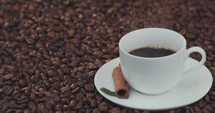 Koffiekop en koffiebonen Een witte kop van verdampende koffie op de lijst met geroosterde boon stock videobeelden