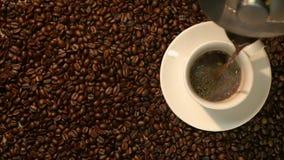 Koffiekop en koffiebonen Een witte kop van verdampende koffie op de lijst met geroosterde boon De langzame Motiekoffie giet stock videobeelden