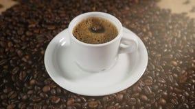 Koffiekop en koffiebonen Een witte kop van verdampende koffie op de lijst met geroosterde boon Super Langzame Motiekoffie stock video