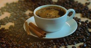 Koffiekop en koffiebonen Een witte kop van verdampende koffie op de lijst met geroosterde boon Voorraadlengte 4K stock footage