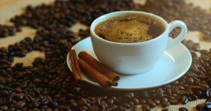 Koffiekop en koffiebonen Een witte kop van verdampende koffie op de lijst met geroosterde boon Voorraadlengte 4K stock video