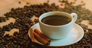 Koffiekop en koffiebonen Een witte kop van verdampende koffie op de lijst met geroosterde boon Voorraadlengte 4K stock videobeelden
