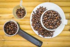 Koffiekop en koffiebonen op bamboeachtergrond Royalty-vrije Stock Foto