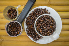 Koffiekop en koffiebonen op bamboeachtergrond Royalty-vrije Stock Foto's