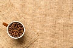 Koffiekop en koffiebonen op de jute Hoogste mening stock afbeelding